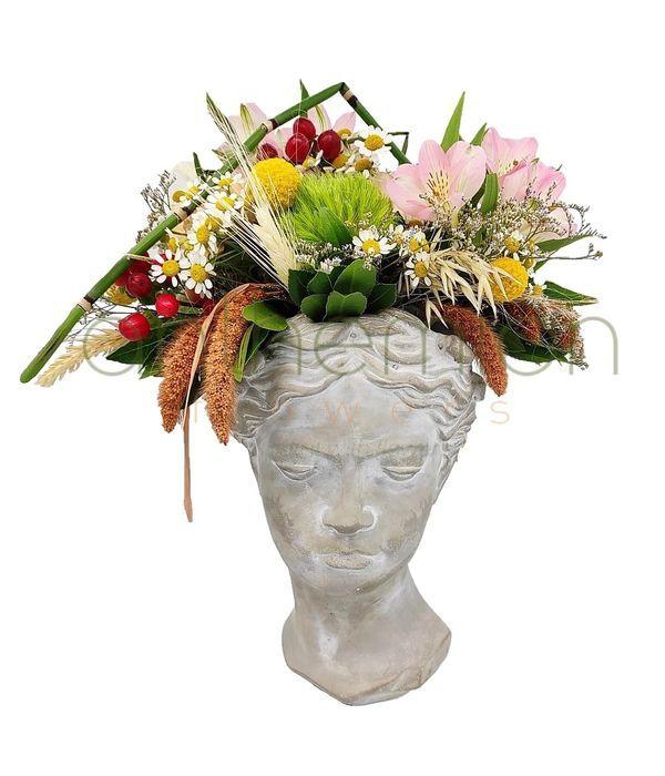 Χαρούμενα λουλούδια σε τσιμεντένιο κεφάλι