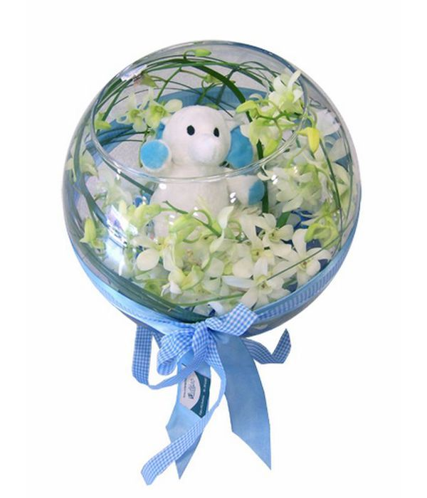 Glass ball with orchids and blue teddy bear