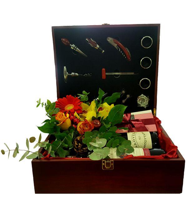 Ξύλινη θήκη με λουλούδια, δύο κρασιά και σοκολατάκια