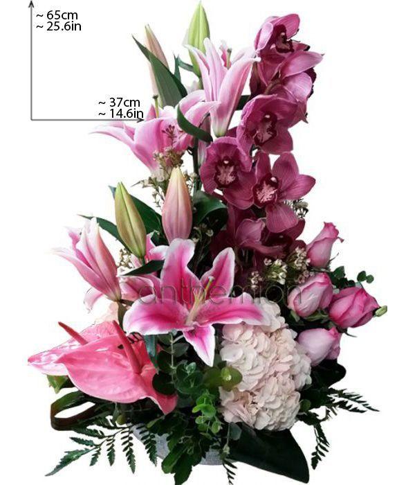 Ψηλή σύνθεση με ροζ και φούξια ορχιδέες και οριεντάλ