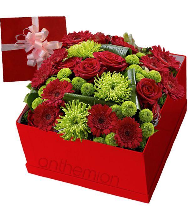 Κόκκινα και πράσινα λουλούδια σε κουτί δώρου