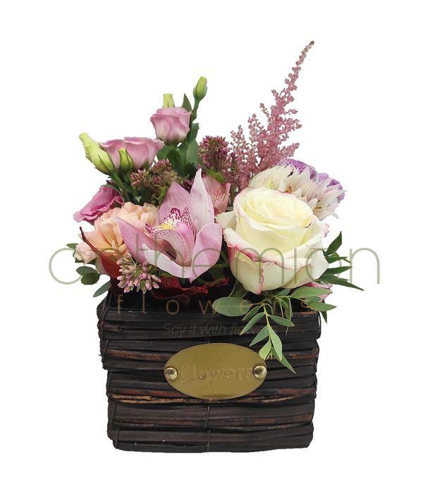 Λουλούδια σε ροζ αποχρώσεις σε ξύλινο κύβο