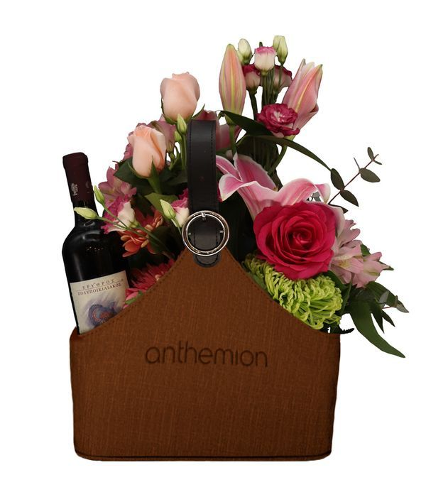 Brown leather newspaper case with a bottle of wine and flowers