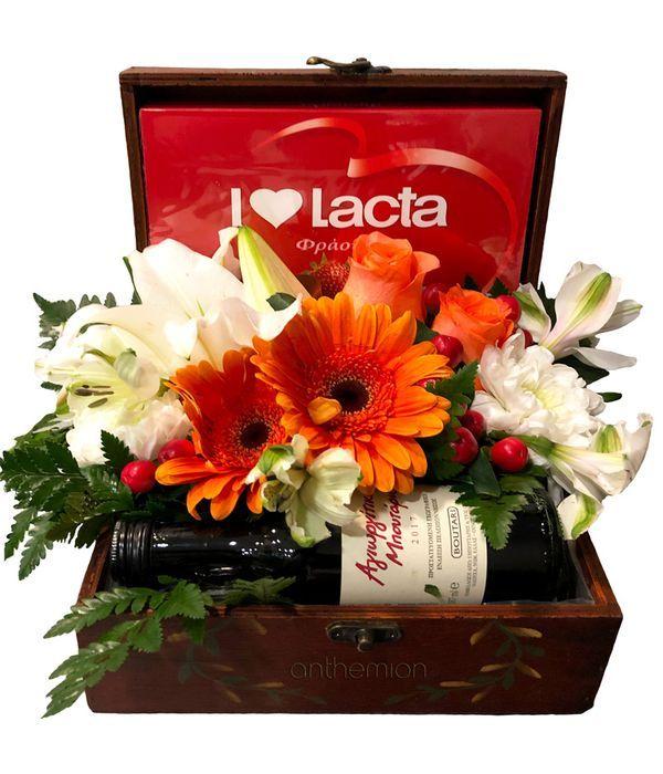 Κρασί λουλούδια και σοκολατάκια σε ξύλινο μπαουλάκι