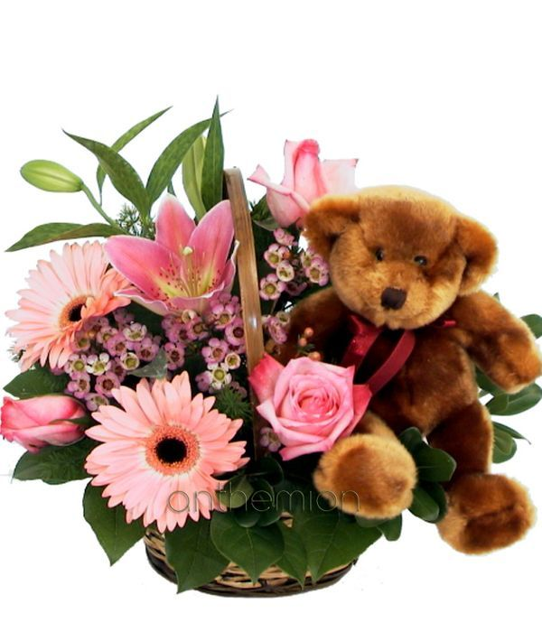 Pink flowers in basket with teddy bear