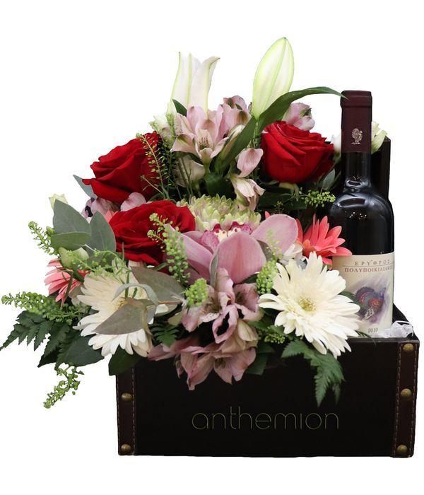 Δερμάτινο μπαούλο με ένα μπουκάλι κρασί και λουλούδια