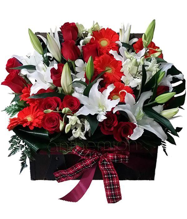 Λευκά, πορτοκαλί και κόκκινα λουλούδια σε μπαουλάκι