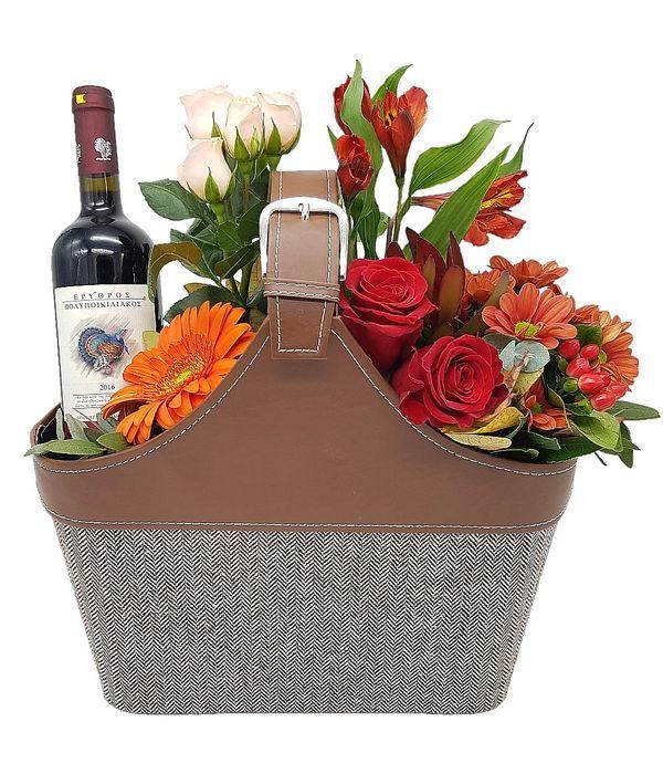 Λουλούδια και κρασί σε δερμάτινη τσάντα
